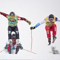 Deux skieurs s'envolent dans les airs.