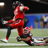 Un joueur de football vêtu de rouge se fait saisir la jambe par un rival lors d'un match de la NCAA.