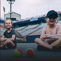 Photo de deux fillettes sur un court de tennis.