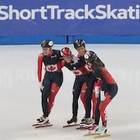 Quatre patineuses s'enlacent après une course.