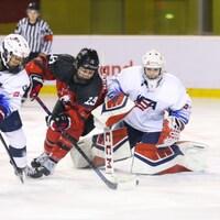 Deux joueuses se disputent la rondelle devant la gardienne américaine.