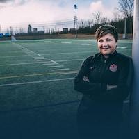 Carol Anne Chénard est appuyée sur un but de soccer et sourit.