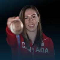 Une femme tend devant une une médaille de bronze olympique et sourit.