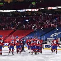 Les joueurs sur la glace saluent la foule en levant leurs bâtons dans les airs.