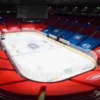 Une bâche rouge et une bâche bleue recouvrent les gradins aux abords de la patinoire. Des logos du Canadien et des commanditaires y sont apposés.