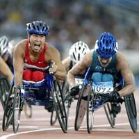 Une athlète en fauteuil roulant exulte après sa course.