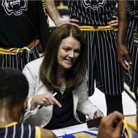 Une entraîneuse de basketball s'adresse à des joueurs.