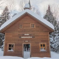 Une maison de bois sous la neige avec une enseigne où il est indiqué, École buissonnière.