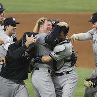 Le lanceur des Yankees est encerclé par ses coéquipiers alors qu'il prend son receveur Kyle Higashioka. Tous sautent de joie.