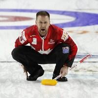 Brad Gushue, accroupi sur la glace, crie ses directives.