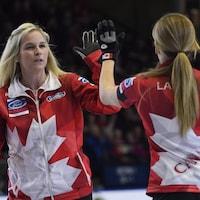 La capitaine canadienne Jennifer Jones (à gauche) célèbre une récolte de trois points avec sa coéquipière Kaitlyn Lawes en demi-finale contre les États-Unis.