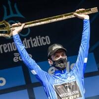 Il soulève le trophée remis au vainqueur.