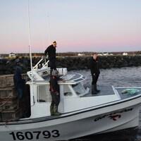 Bateau au quai, avec casiers de homards. Quatre personnes sont sur l'embarcation. Le jeune Doucet est à l'avant, regardant vers la mer.