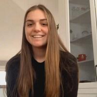 Jeune femme assise dans une cuisine, souriante.