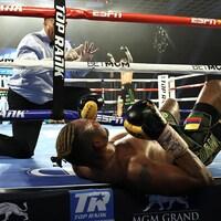 Un arbitre donne le compte à un boxeur couché sur le dos.