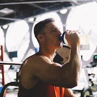 Un homme, dans une salle d'entraînement, boit dans une bouteille