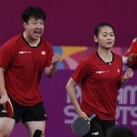 Un homme et une femme célèbrent un point au tennis de table.