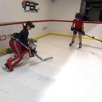Une femme gardienne de but et un jeune homme s'entraînent au hockey avec un casque de réalité virtuelle.