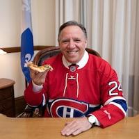 François Legault, portant un chandail du Canadien, tient une pointe de pizza dans la main.