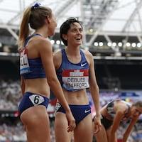 Elle sourit avec une adversaire après sa course.