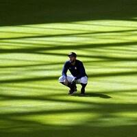 George Springer se trouve dans le champ centre d'un terrain de baseball. Il est accroupi.