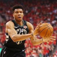 Il est en possession du ballon dans l'uniforme des Bucks de Milwaukee.