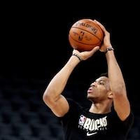 Il tient le ballon à deux mains au-dessus de sa tête.
