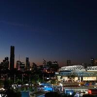 Vue générale du centre-ville de Melbourne le soir, avec un stade éclairé à l'avant-plan.