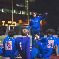 Un entraîneur de soccer parle à ses joueurs durant la mi-temps.