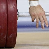 Gros plan des mains d'un haltérophile qui s'apprête à soulever une charge
