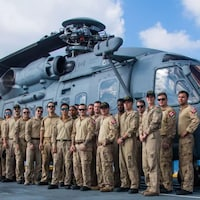 20 membres de l'équipage posent devant l'hélicoptère.