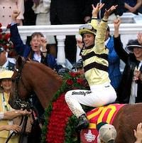 Le jockey, bien en selle, lève les bras dans le cercle du vainqueur.