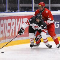 Le Canadien Peyton Krebs (à l'avant) tente de maîtriser la rondelle devant Anton Sedov, du Bélarus.