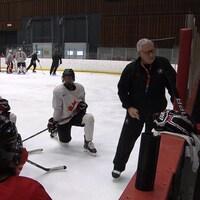 L'entraîneur donne des directives aux hockeyeuses canadiennes.