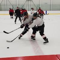 Deux hockeyeuses bataillant pour la rondelle pendant le camp d'entraînement