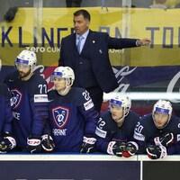 L'entraîneur dirige ses joueurs derrière le banc