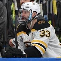 Zdeno Chara assis au banc des Bruins, avec un protecteur facial