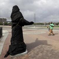 Un homme regarde la statue de Kate Smith, couverte d'une bâche, à l'extérieur du Wells Fargo Center.