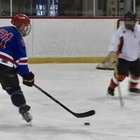 Un joueur de hockey mineur fait face à un autre joueur et au gardien, sur la glace.