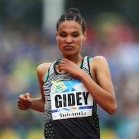 La coureuse en pleine action avec une expression de sérieuse concentration sur le visage.