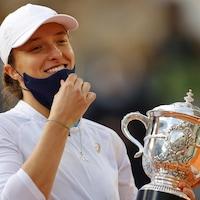 Iga Swiatek sourit avec en main le trophée Suzanne Lenglen qui récompense la lauréate des Internationaux de France