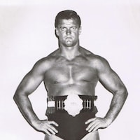 Il pose, torse nu, avec sa ceinture de champion de lutte.