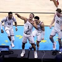 Un joueur de basketball sur une table est félicité par ses coéquipiers