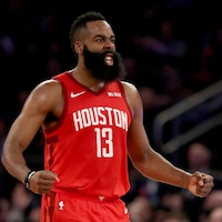 Portant l'uniforme rouge des Rockets de Houston, James Harden, le visage crispé et les bras contractés, célèbre.