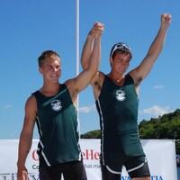 Deux jeunes hommes lèvent les bras en signe de victoire debout sur un podium au bord de l'eau.