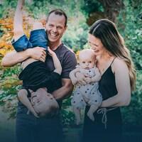 Jean-Luc Brassard tient son fils Grey, qui rit, sous le regard de sa conjointe Shana et de leur fille Ciel.