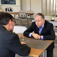 Il répond aux questions du journaliste assis à une table.