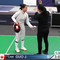 Elle présente son fleuret à l'arbitre avant un duel.