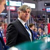 Homme au regard songeur debout derrière des joueurs de hockey.