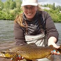 Une femme dans un lac avec un poisson dans ses mains.